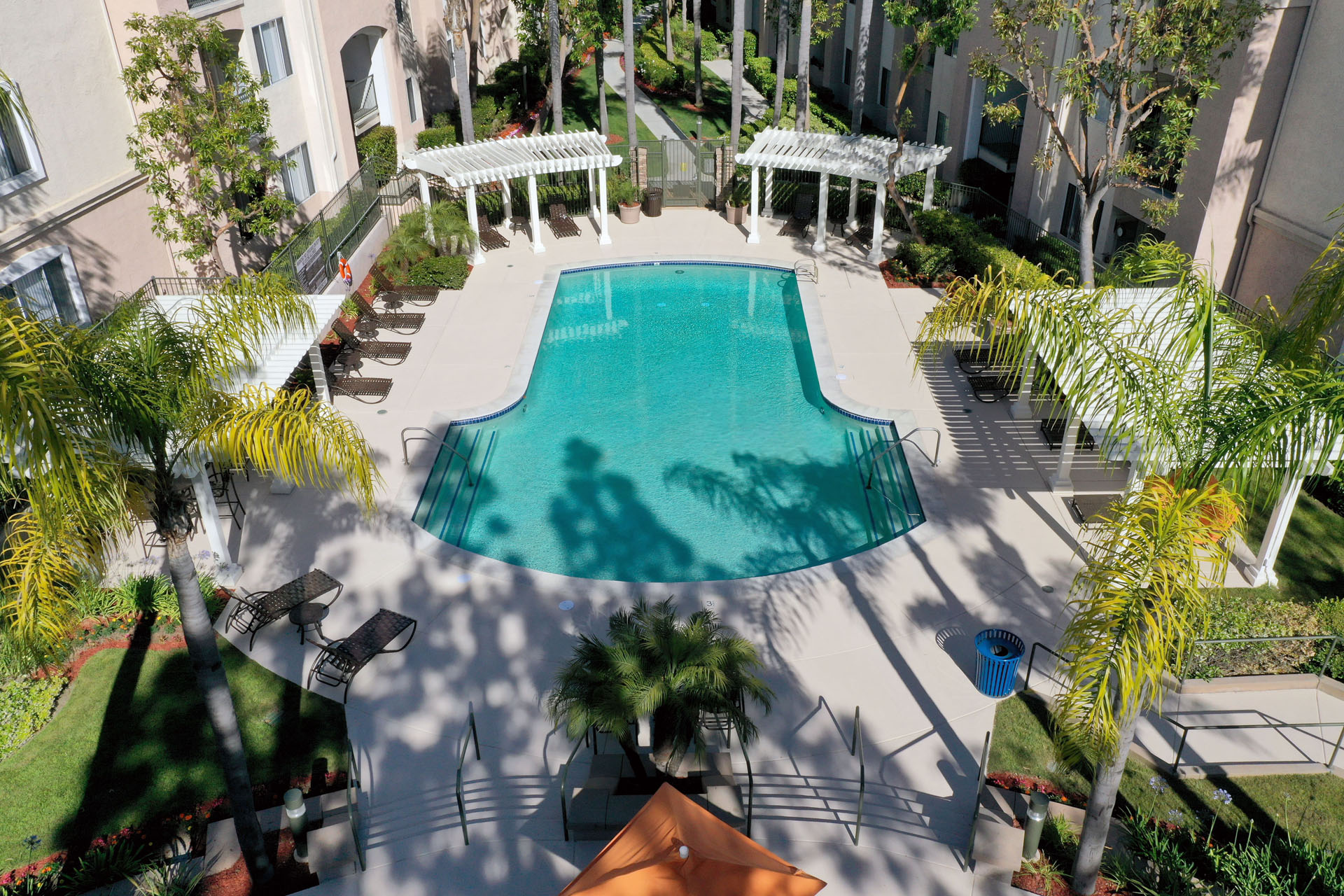 Apartments in Aliso Viejo CA-Aventine Apartments Swimming Pool Surrounded by Palm Trees, Lounge Chairs, and Gazebos